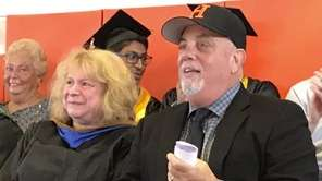 Billy Joel, right, sits during the Hicksville High