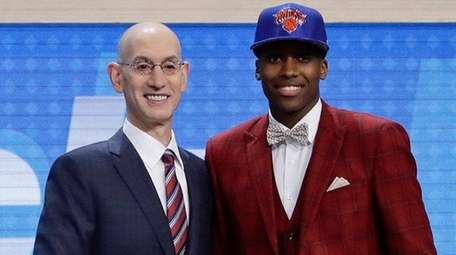 Frank Ntilikina, right, poses with Adam Silver after