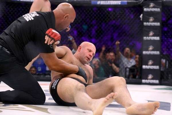 Fedor Emelianenko is tended to by the ref