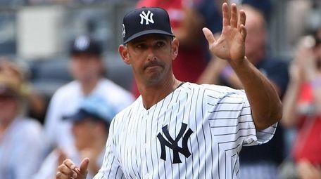 Former Yankees catcher Jorge Posada waves to crowd