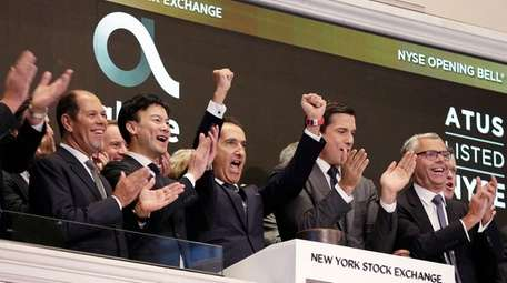 Altice founder Patrick Drahi, center, after ringing the