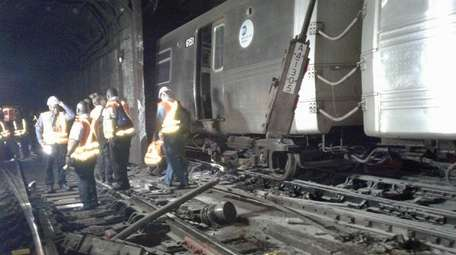 Workers examine damage at the West 125th Street