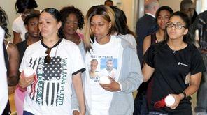 Lina Garriques, center, mother of Anthony Holmes-Garriques, arrives