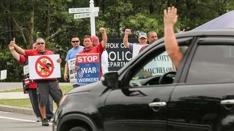 A passing motorist responds to striking employees of