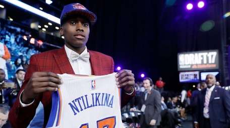 Frank Ntilikina holds up his jersey after being