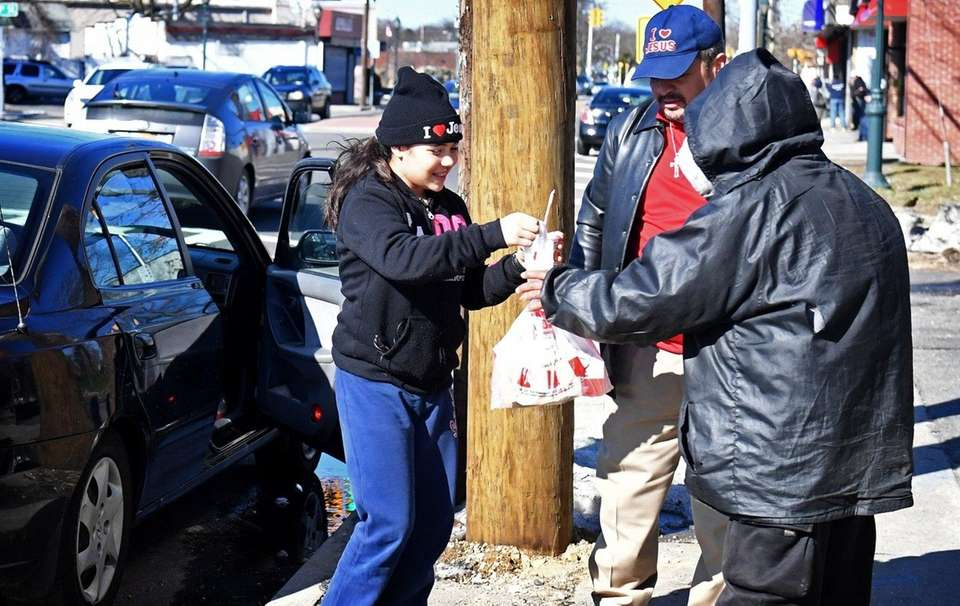 Lydia Pacheco of Copiague distributes KFC to the