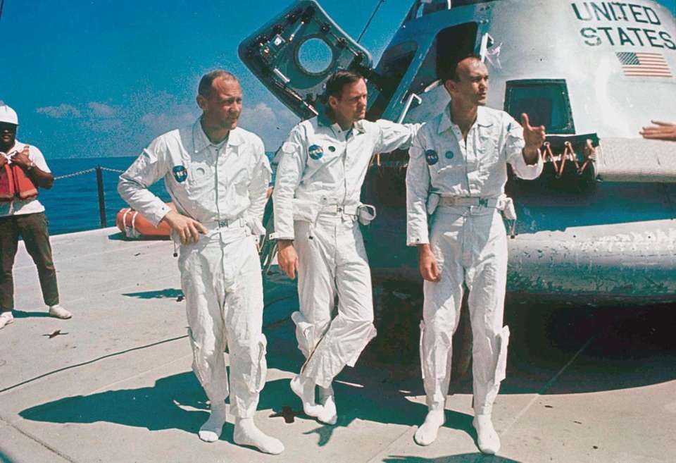 Apollo 11 astronauts stand next to their spacecraft