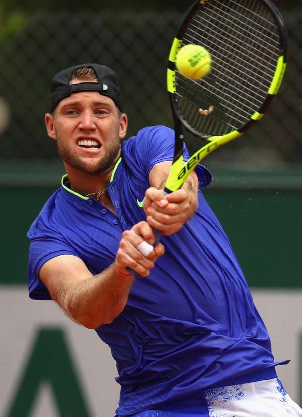 Jack Sock plays a backhand against Jiri Vesely