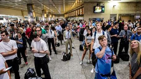 Passengers watch the LIRR departures board in Penn