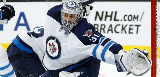 Jets goalie Ondrej Pavelec moves to make a