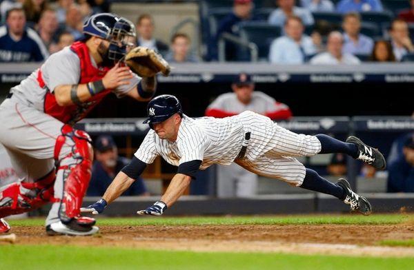 Brett Gardnerof the Yankees dives home for a