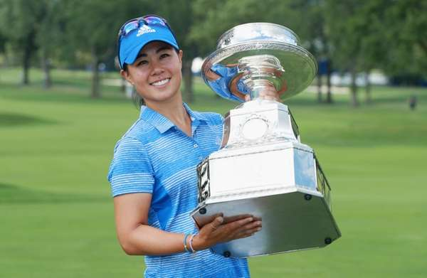 Danielle Kang poses with the trophy after winning