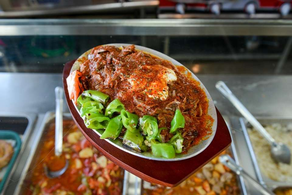 Iskender kebab, garnished with tomato sauce and yogurt,