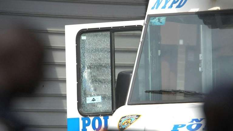 A bullet-shattered window can be seen in the