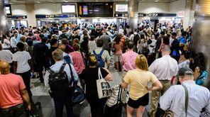 Passengers near the LIRR departures board in Penn