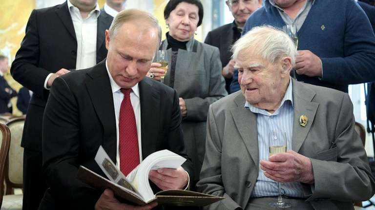 Russian President Vladimir Putin, left, and author Daniil