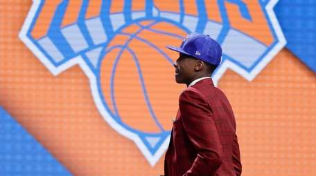 Frank Ntilikina walks up on stage after being