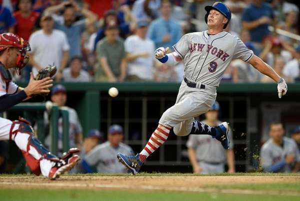 The Mets' Brandon Nimmo runs home against Nationals catcher