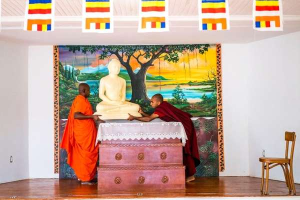 Bhante Nanda, left, and another man place a