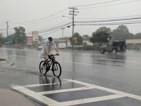 A bicyclist sloshes through the rain on Old