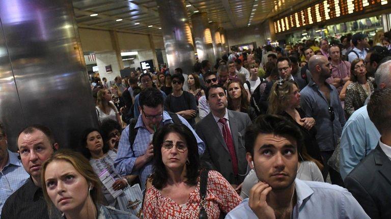 Long Island Rail Road passengers wait for the
