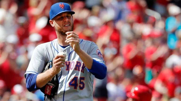 Mets pitcher Zack Wheeler, left, reacts as the