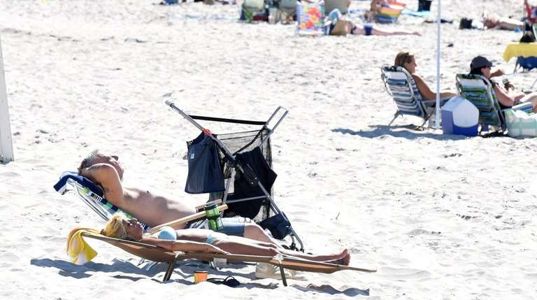 Sunbathers at Smithpoint County Beach on Sunday, July
