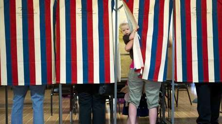 Landon Peterson peeks out of the voting booth