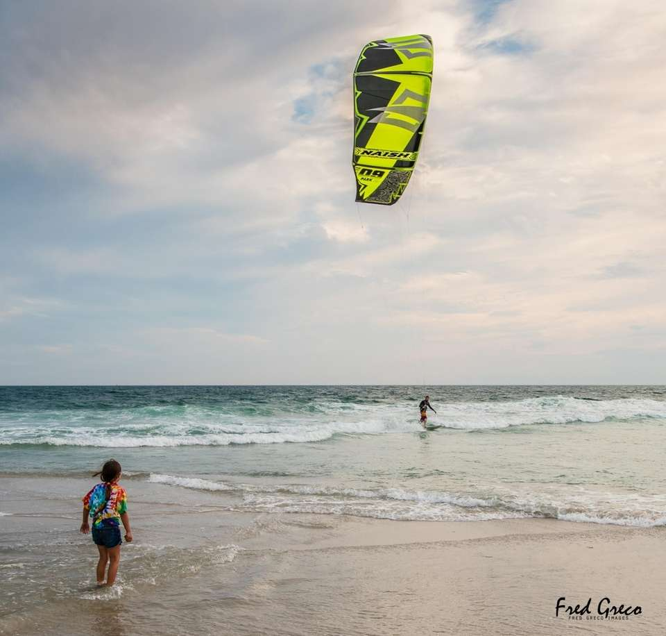 Esme Greco, age 7, watches kite surfers at