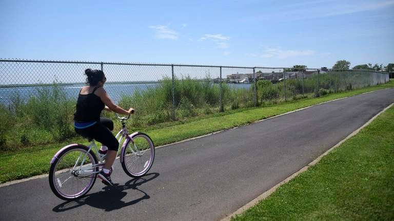 A woman rides the bike path along the