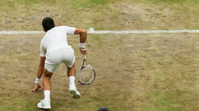 Serbia's Novak Djokovic slips on the baseline as