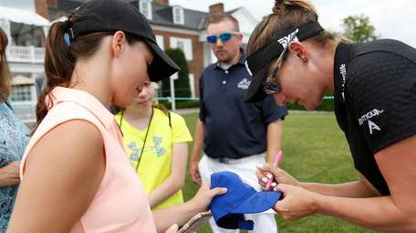 Brittany Lang signs a hat for a fan