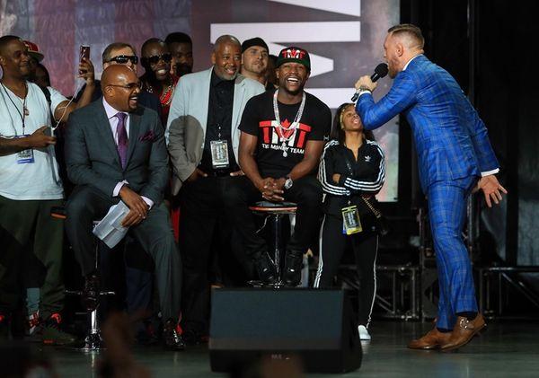 Conor McGregor speaks to Floyd Mayweather Jr. during