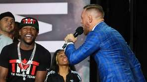Conor McGregor speaks to Floyd Mayweather Jr. during