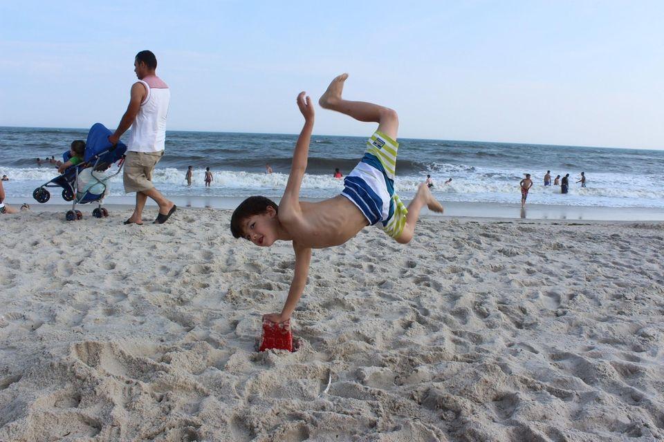 Sammy Tom (7) flipping over summer sand castle