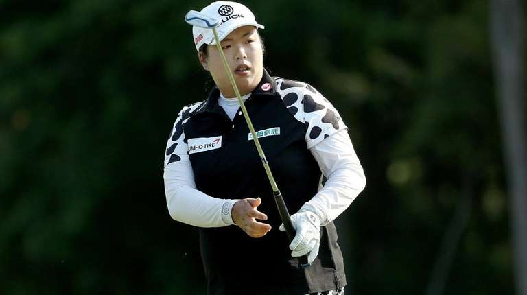 Shanshan Feng of China watches her shot on