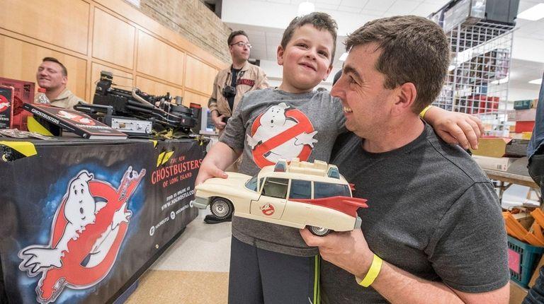 A little boy wearing a Ghostbusters t-shirt is