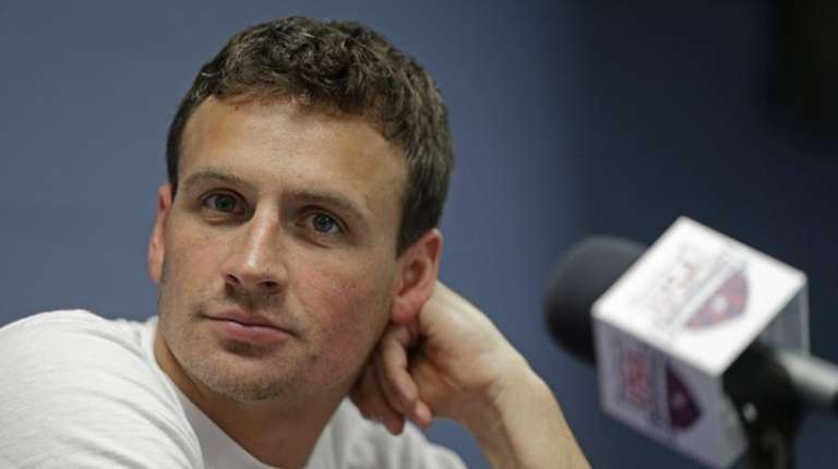 Ryan Lochte listens to a question from the
