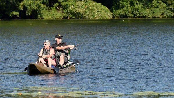 A couple enjoys fishing on a kayak on