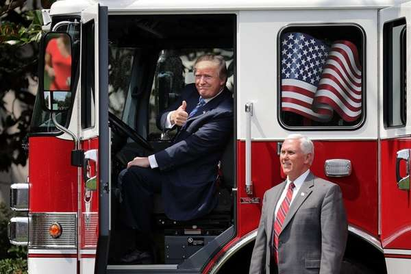 President Donald Trump sits in a fire engine