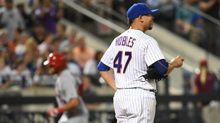 Metspitcher Hansel Robles stands on the mound after