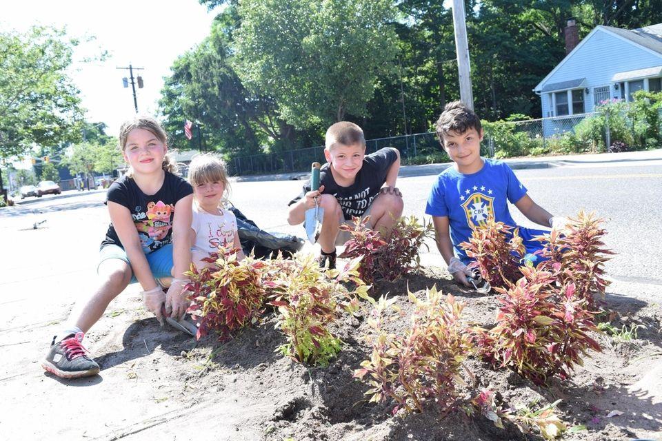 Kids helping plant flowers.