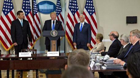 U.S. President Donald Trump, center, speaks as Vice