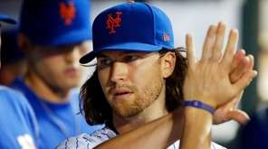 Jacob deGrom of the Mets walks through the dugout