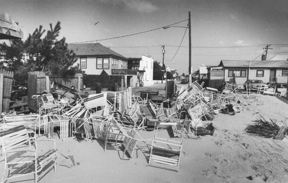 Beach chairs are piled up in the sand