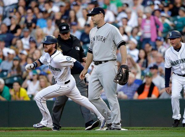 The Mariners' Ben Gamel, left, races past Yankees