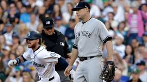 The Mariners' Ben Gamel, left, races past Yankees