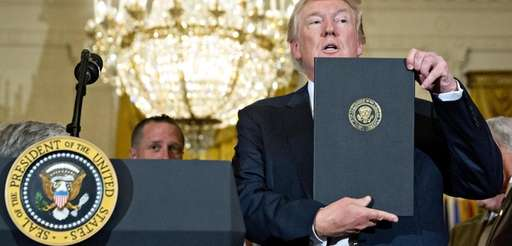 President Donald Trump holds up a