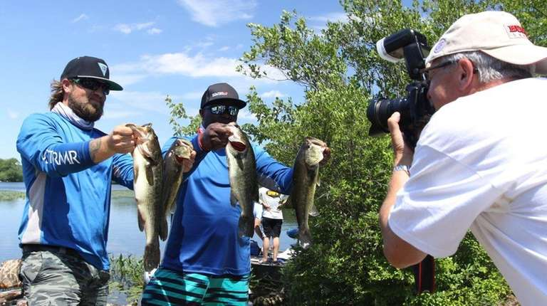Two fishermen show off their largemouth bass at