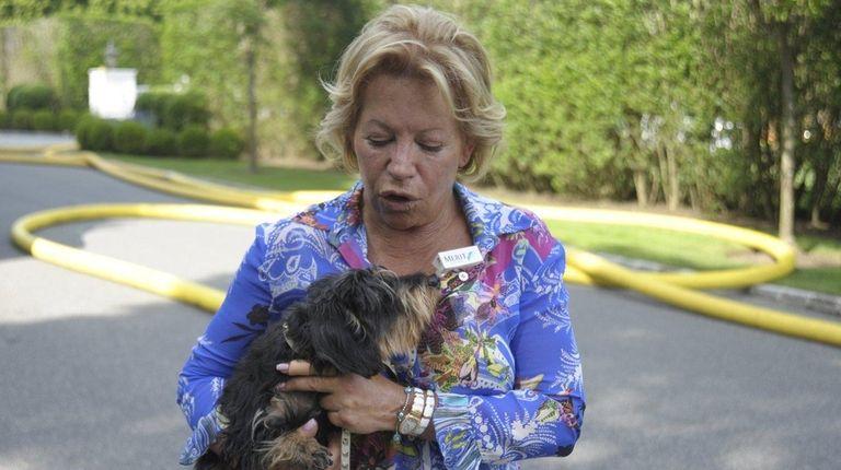 Homeowner Jamie Kepferman calms her dog Quincy after